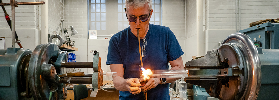 A photo of the chemistry department's glassblower blowing glass